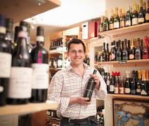 Wine merchant with wine bottle in shop - stock photo