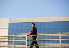 Businessman carrying folder on walkway Stock Photos