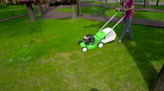 A Man With an Electric Lawn Mower Stock Footage