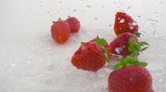 Strawberries falling splashing on water slow motion Stock Footage