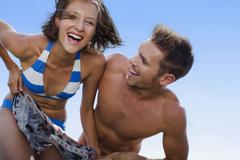 Couple playing on beach together Stock Photos