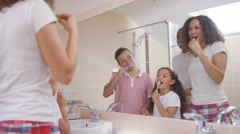 4K Happy mixed race family in bathroom brushing their teeth togethe Arkistovideo