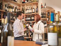 Wine merchant with customer in shop - stock photo