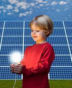Boy with light bulb by solar panel Kuvituskuvat
