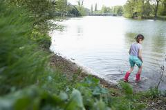 Girl in rainboots wading in pond - stock photo