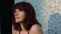 4k video of a woman outdoors daydreaming and smiling at sun Stock Footage