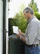 Man reading instructions in backyard Stock Photos