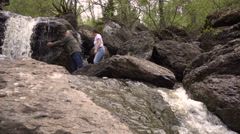 Couple Man and Woman Drinking From a Waterfall Splash Water at Each Other - stock footage