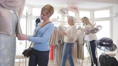 4K 3 female generations of a family shopping for outfits in a bridal wear store. - stock footage