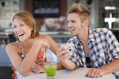 Couple admiring photos at cafe - stock photo