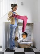Woman unloading clothes from dryer - stock photo