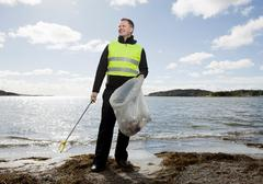 Worker in safety vest cleaning beach Stock Photos