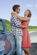 Couple hugging by convertible Stock Photos