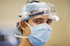 Surgeon wearing mask and headlamp Stock Photos