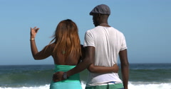 4K Happy couple holding hands as they walk along the beach Stock Footage