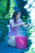 Woman pruning plants in garden Stock Photos