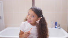 4K Little girl in bathroom cleaning her teeth, as seen from the mirror's pov Stock Footage
