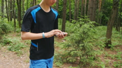 Young man using fitness bracelet during morning run Stock Footage