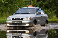 CHERKASSY, UKRAINE- JUNE 5, 2016: cars driving on a flooded road during a flood - stock photo