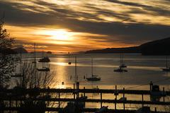 Silhouetted boats on sea, Salt Spring Island, British Columbia, Canada - stock photo