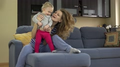 Beautiful woman tickle toddle child stomach sitting on sofa Stock Footage