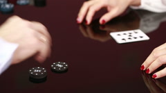 Dealer handling playing cards at a poker table. Black background Stock Footage