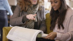 4K Young woman with sales assistant looking at fabrics in home furnishings store - stock footage