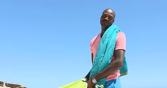 4K Portrait smiling South African man putting up parasol for shade at the beach Stock Footage