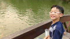 boy feeding fish in the pond. - stock footage