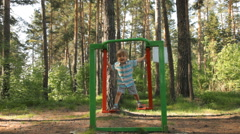 Little boy playing on gymnastic equipment in park - stock footage