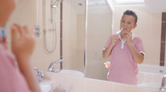 4K Cute young brother & sister in bathroom, looking in mirror & brushing teeth Stock Footage