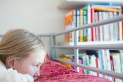 Young wistful girl lying on bed Stock Photos