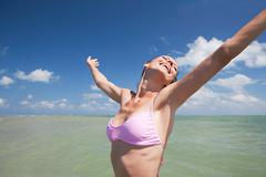 Young woman in sea with arms out, portrait Stock Photos