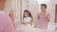4K Cute young brother & sister in bathroom, looking in mirror & brushing teeth Arkistovideo