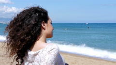 Happy young woman with beautiful hair enjoying the summer sun on the sea shore Stock Footage