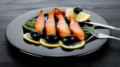 Grilled salmon slices with asparagus lemon olives and cutlery Stock Footage