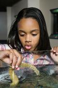 Girl holding marine plant in aquarium Stock Photos
