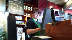 Customer buying coffee and paying gift card at Starbucks Stock Footage