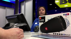 Man buying JBL bluetooth speaker and taking receipt back inside Best buy store Stock Footage