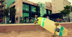 Skateboard lying on sand at city street. Closeup. Time lapse. Urban scene Stock Footage