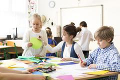 Happy pupils painting the pictures during art classes at school. Sitting with fr Stock Photos