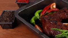 Baked big beef meat rib chunk under sweet sauce with tomatoes Stock Footage