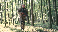 Military man starts to shoot in the forest - stock footage
