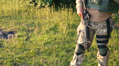 Military man arms automaton in the steppe - stock footage