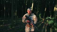 Tired soldier goes in the forest - stock footage