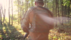 Strong young military goes in the forest and looks back - stock footage