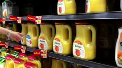 Woman buying Tropicana orange juice inside Walmart store Stock Footage