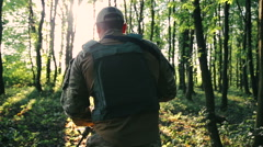 Armed young military goes in the forest and looks back - stock footage