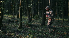 Armed young military steps in the forest and looks back - stock footage