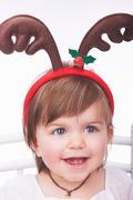 Baby girl wearing reindeer antlers Stock Photos